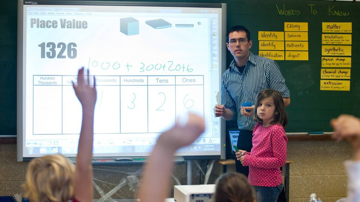 Teacher Daniel Rolo uses a smart board with student Lauren Dos Santos during a math lesson.