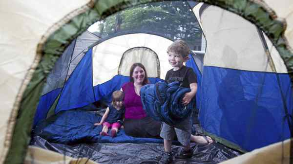 Four year old Dante carries a sleeping bag into their tent as mom Kerrie Palmer , and two year old sister Rose, look on.