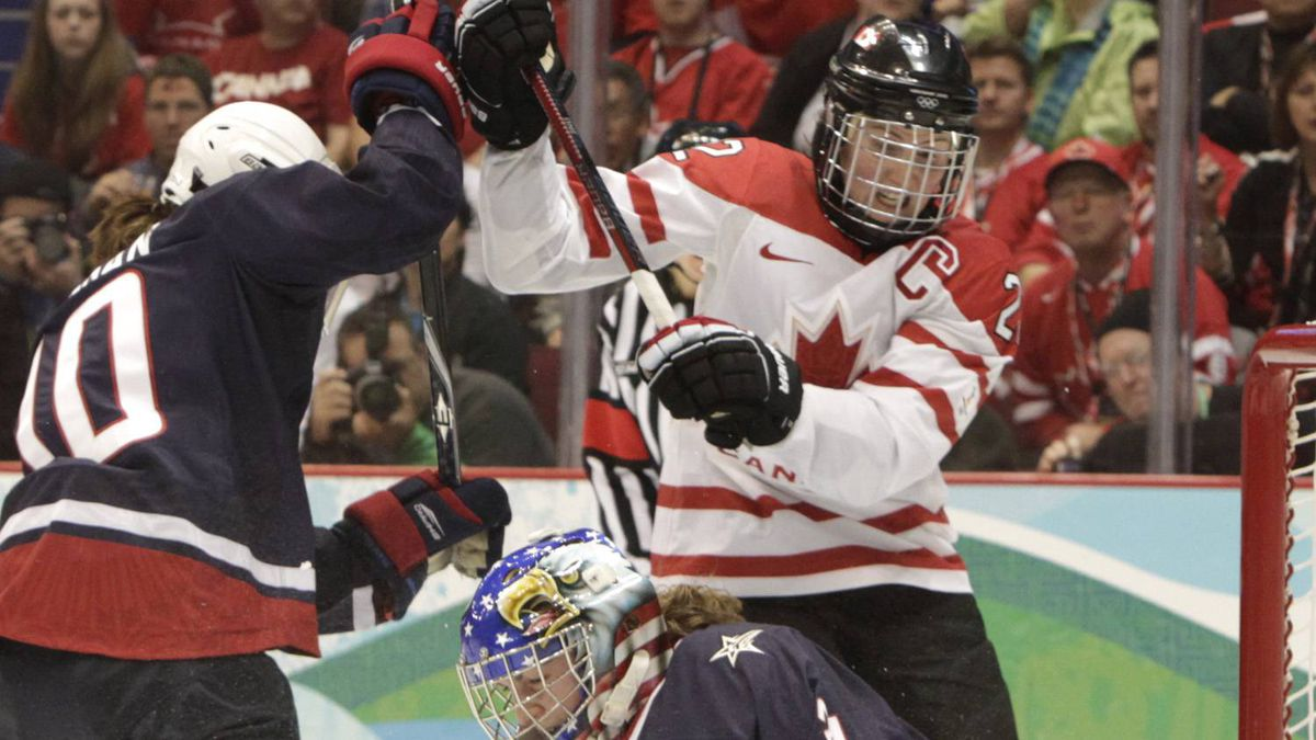 Canada's Hayley Wickenheiser battles for position with USA's Meghan Duggan while USA's Jessie Vetter makes a save at the Vancouver Olympics.