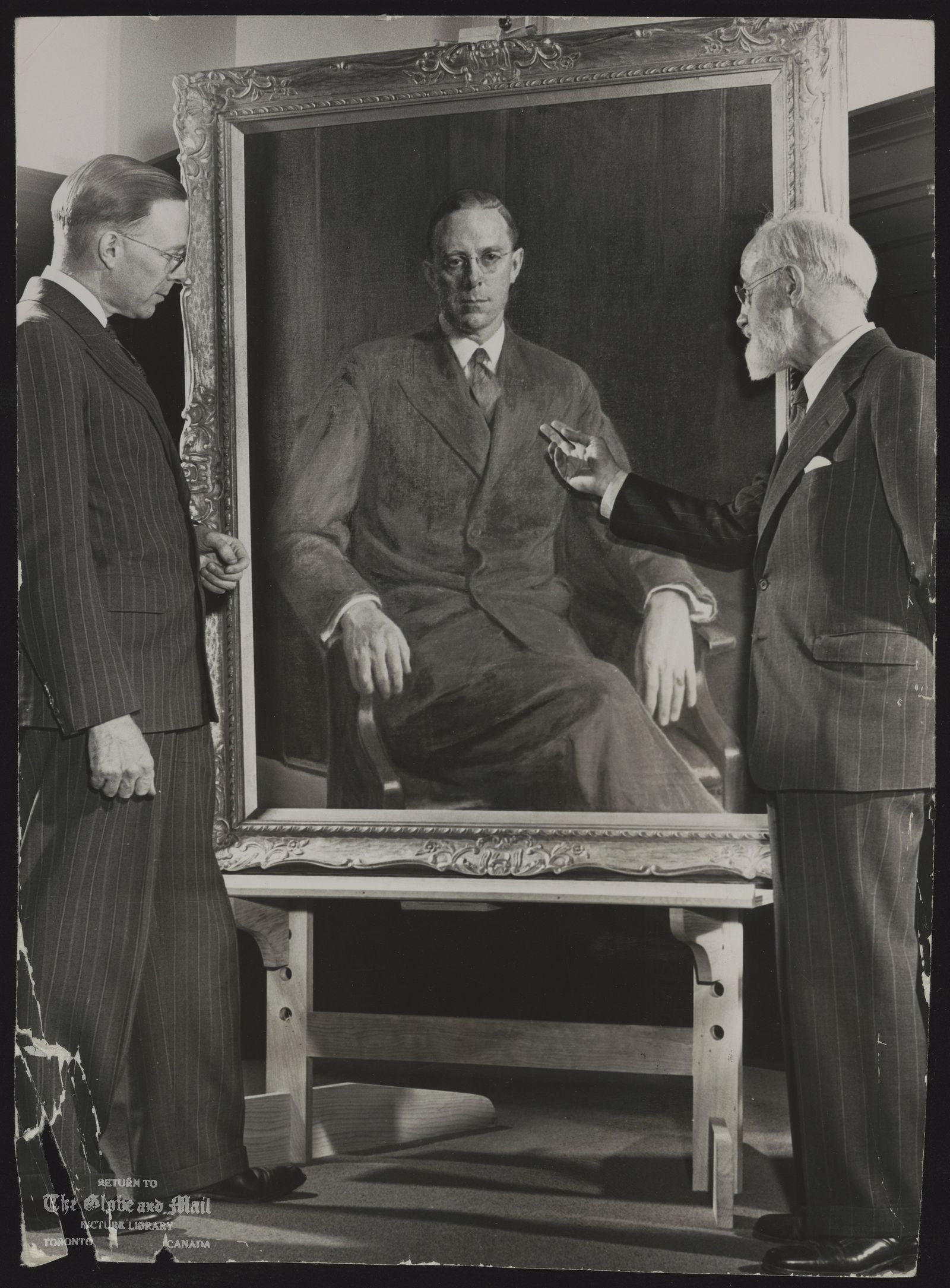 E.C. MANNING Alberta PORTRAIT DONE---Premier E.C. Manning of Alberta, left, and Ernest Fosbery, R.C.A., of Montreal, study the premier's portrait recently completed by Mr. Fosbery. The painting was commissioned privately by member of the Alberta cabinet.