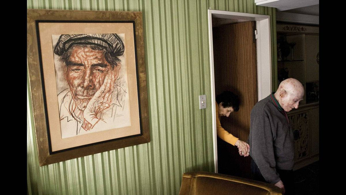 """Alejandro Kirchuk of Argentina has won the first prize Daily Life Stories, with the series """"Never Let You Go"""". Marcos leads Monica from their room to the living room. Although at times he grumbles about the time devoted to her care, Marcos did not see any other possibility. """"Tell me where she is going to be better than here. I treat her like a princess, here she has everything."""" Marcos, 89, and Monica, 87, have been married and living in their apartment in Buenos Aires, Argentina, for 65 years. In 2007, Monica was diagnosed with Alzheimer's disease. Since that moment, her husband devoted all his time to take care of her. The disease is considered a future epidemic because it mainly affects older people, and as life expectancy is annually increasing in global population, the disease is becoming increasingly common."""