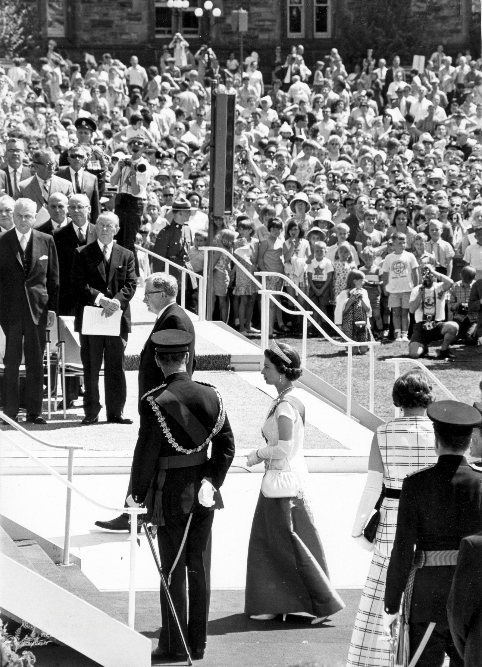 JULY 1, 1967 -- ROYALS CELEBRATE CANADA'S CENTENNIAL -- There was a formal but tumultuous welcome for Queen Elizabeth II and Prince Philip when they arrived on Parliament Hill in Ottawa for the morning ecumenical service on Canada's 100th birthday. The religious service, conducted by eight clergymen from various Christian denominations and the Jewish faith, began immediately upon her arrival. Her Majesty wore a long royal blue and white dress embroidered in a maple leaf design in diamonds and sapphires, with a diamond-fringe tiara, the blue sash and star of the Order of the Garter and family orders. Prince Philip was dressed in the uniform of colonel-in-chief of the Royal Canadian Regiment. Photo by John McNeill / The Globe and Mail Originally published July 3, 1967, page A8.