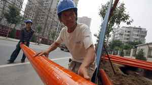 Workers move piping at a construction site in Beijing.