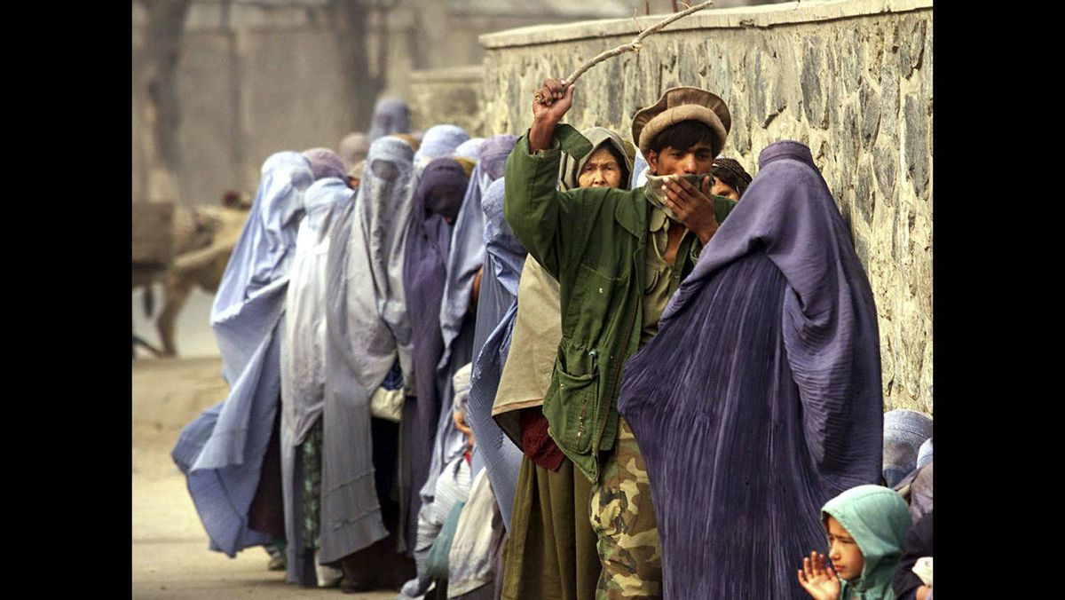 An Afghan soldier uses a wooden stick to maintain order among women waiting for humanitarian aid at a World Food Programme (WFP) distribution point in Kabul, December 14, 2001.
