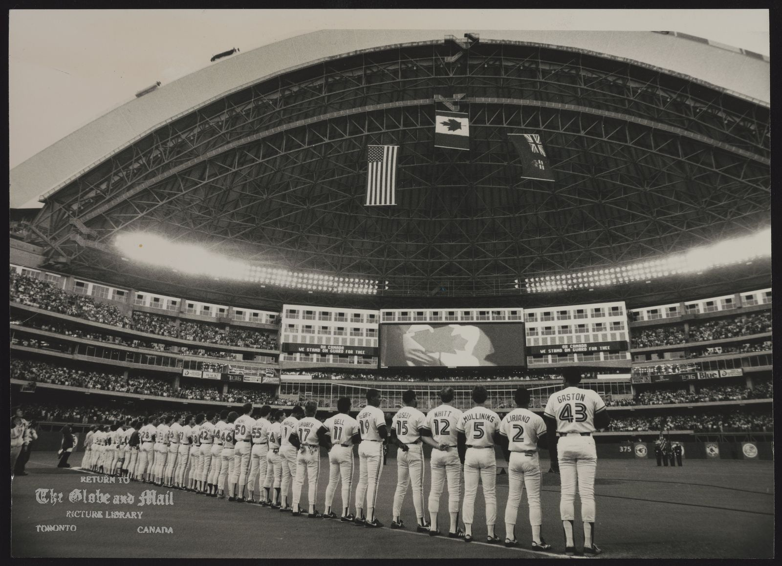 SKYDOME (TORONTO) WITH THE TORONTO BLUE JAYS LINING THE FOUL LINE, THE FLAGS FLAPPING AND THE ROOF ROLLED BACK.