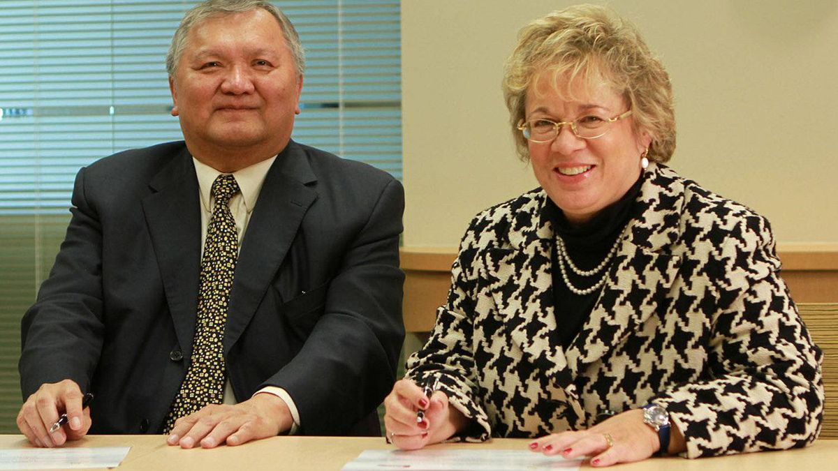 Gitxsan Hereditary Chief Elmer Derrick signs historic equity agreement with Janet Holder, Executive Vice President of Western Access for Enbridge.