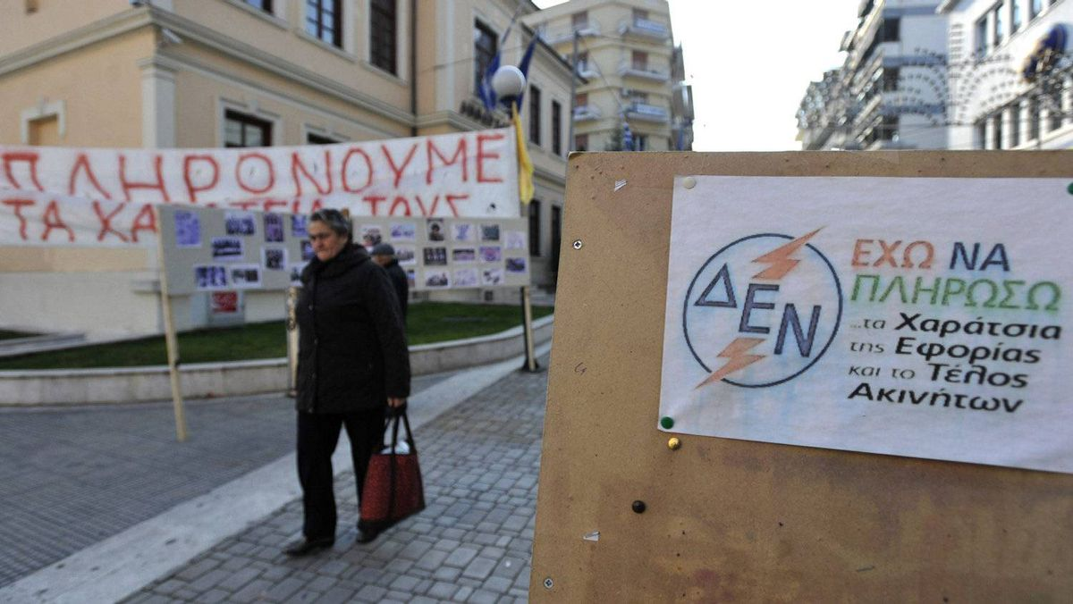 A sign playing on the Greek acronym of dominant electricity producer Public Power Corporation reads 'I can't pay additional taxes and the property levy,' in central Veria, northern Greece, on Friday, Nov. 18, 2011. As two years of pay cuts and tax hikes pummel living standards in debt-crippled Greece, many in this northern town can't pay for basic utilities such as electricity - and get cut off from the grid.