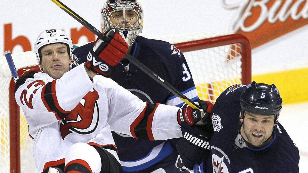 Winnipeg Jets defenceman Mark Stuart (5) checks New Jersey Devils forward David Clarkson (23) in front of Jets goaltender Ondrej Pavelec (31) during second period NHL action in Winnipeg on Saturday, December 3, 2011. The Jets won 4-2. THE CANADIAN PRESS/John Woods