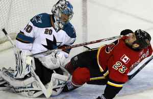 Calgary Flames Eric Nystorm slides into San Jose Shark goaltender Evgeni Nabokov during the first period of their NHL hockey game in Calgary, Alberta, April 6, 2009. REUTERS/Jack Cusano