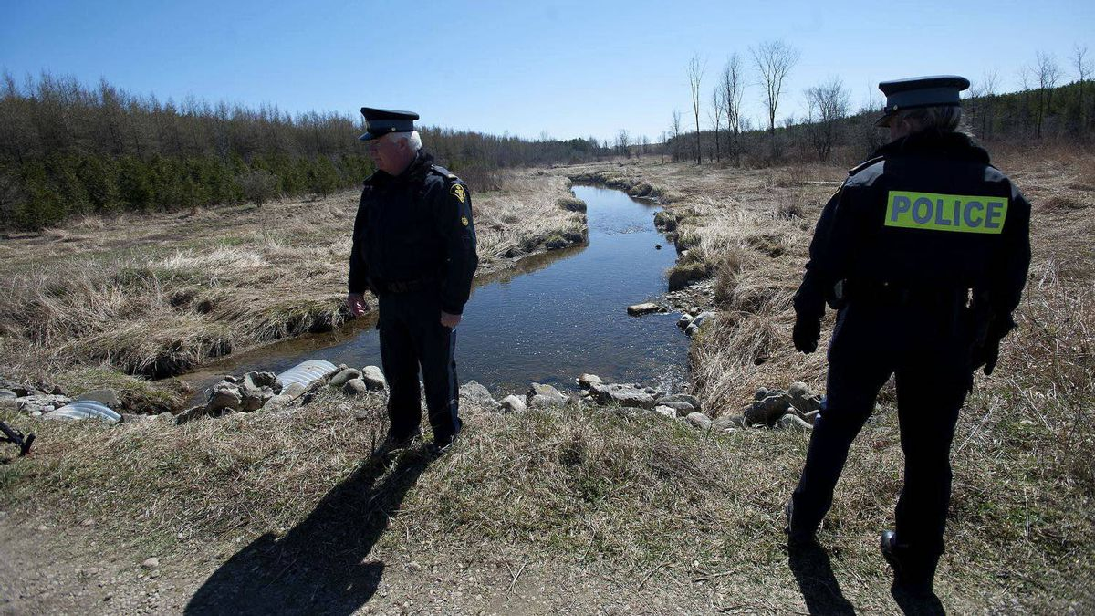 OPP officers are seen at a small creek near the site where Tori Stafford's body was found near Mount Forest, Ont.