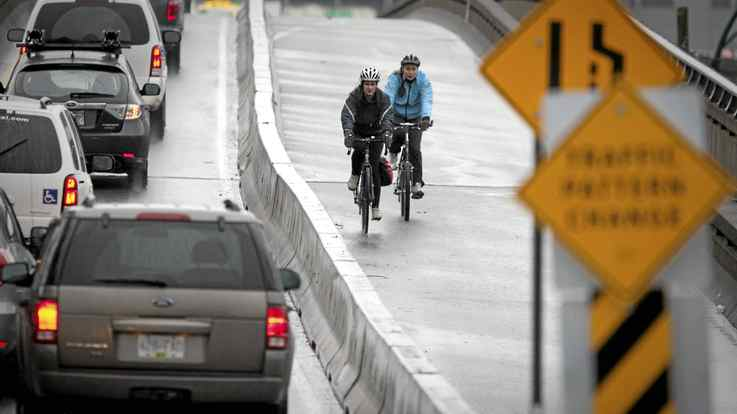 Cyclists rides across the new two-way bike lane separated from traffic on the Dunsmuir Viaduct in Vancouver March 10, 2010.