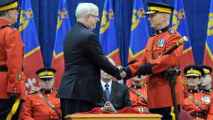 Outgoing RCMP chief William Elliott shakes hands with new Commissioner Bob Paulson during a change-of-command ceremony in Ottawa on Dec. 8, 2011.