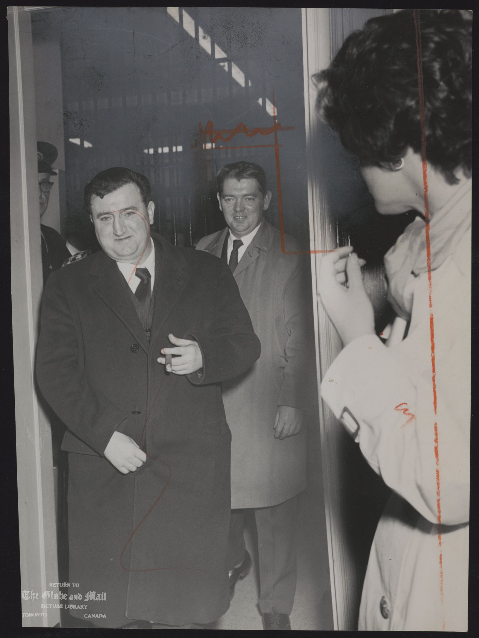 The notes transcribed from the back of this photograph are as follows: EAMONN MARTIN (background) Eamonn Martin with Brendan Behan, playwright. Behan leaving the court room after remand. He was relased on $1,100 bail yesterday, posted by Martin