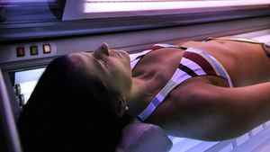 In this Wednesday, Dec. 14, 2005 file photo, a woman lies in a tanning booth in Anchorage, Alaska. International cancer experts have moved tanning beds and other sources of ultraviolet radiation into the top cancer risk category, deeming them as deadly as arsenic and mustard gas. The research was published online in the medical journal Lancet Oncology on Wednesday, July 29, 2009, by experts at the International Agency for Research on Cancer in Lyon, the cancer arm of the World Health Organization.