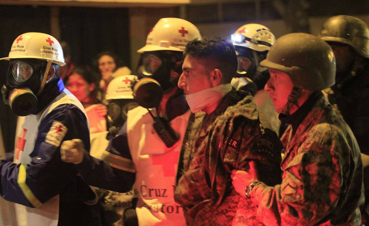 Red Cross medics escort an army soldier injured in clashes with striking police outside a hospital, where Ecuador's President Rafael Correa was holed up inside, in Quito. Guillermo Granja/Reuters