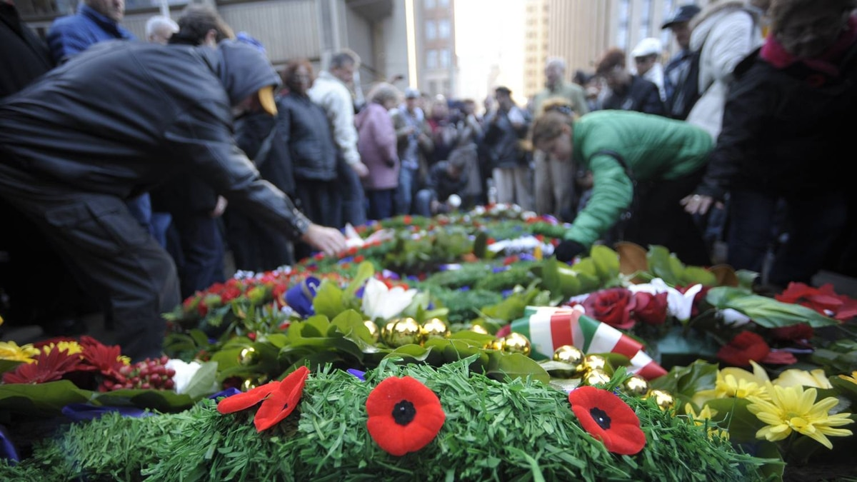 People place their poppies on the wreaths after Remembrance Day ceremonies at Old City Hall in Toronto on Nov 11 2010.