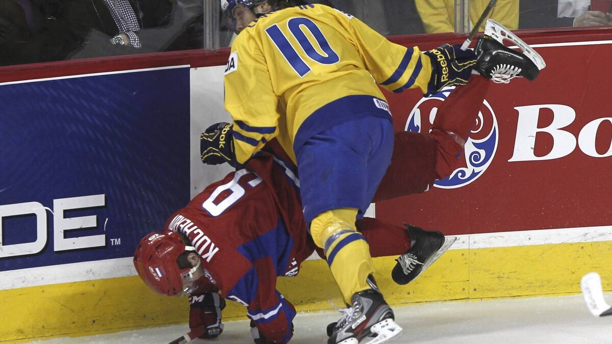 Sweden's Johan Larsson hits Russia's Nikita Kucherov in the first period.