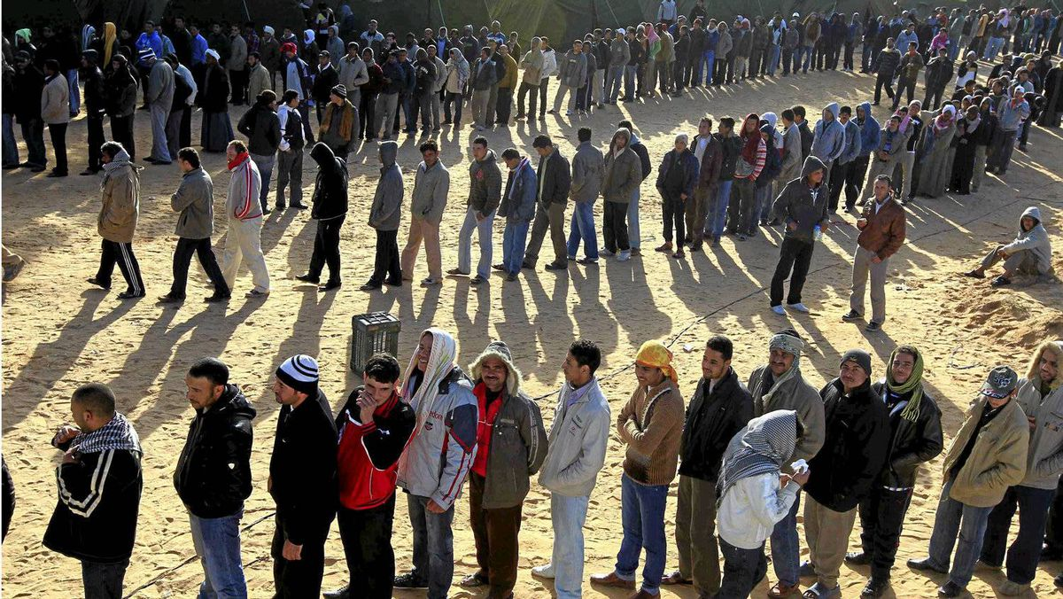 Men who have fled the violence in Libya line up for food at a camp near the Tunisian border crossing of Ras Ajdir on Monday.