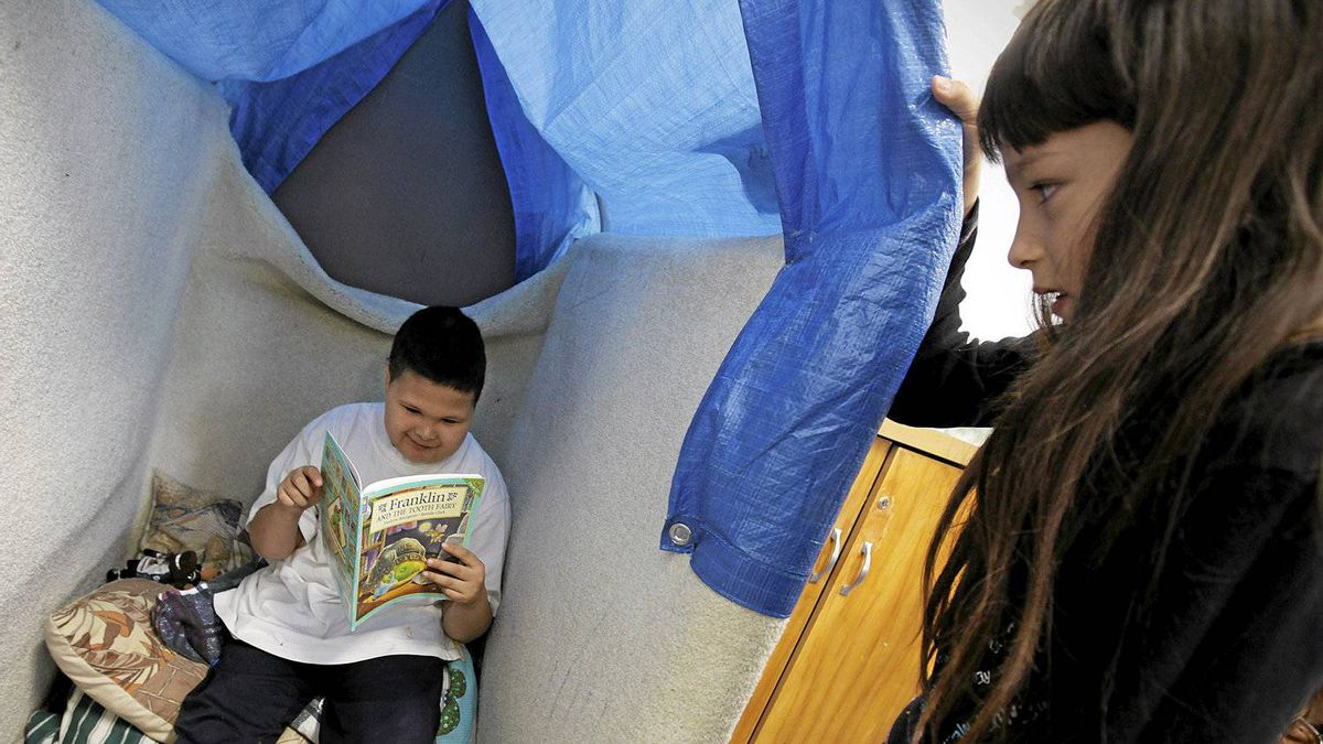 """Monique Michelle watches as Jesse George choses to sit in the """"bunny hole"""" to read her book in a special FASD program at David Livingston Community School in Winnipeg, Tuesday, May 11, 2010."""