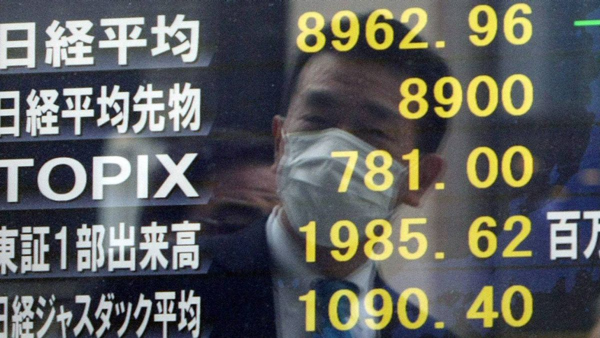 A businessman is reflected on a board showing prices on the Tokyo Stock Exchange.