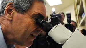 Liberal Leader Michael Ignatieff peers through a microscope at a Kingston lab during a campaign stop on April 11, 2011.