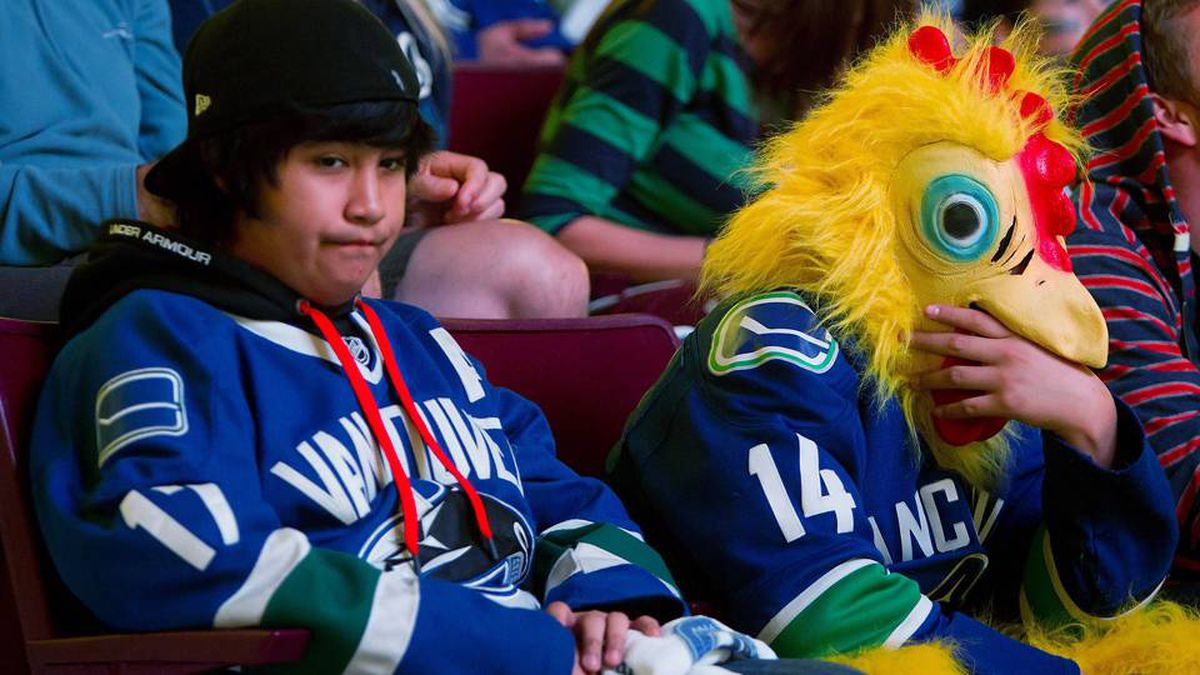 Vancouver Canucks - fans including one wearing a chicken suit - react after a Boston Bruins goal while watching Game 6 of the NHL Stanley Cup Final on the scoreboard at Rogers Arena in Vancouver.