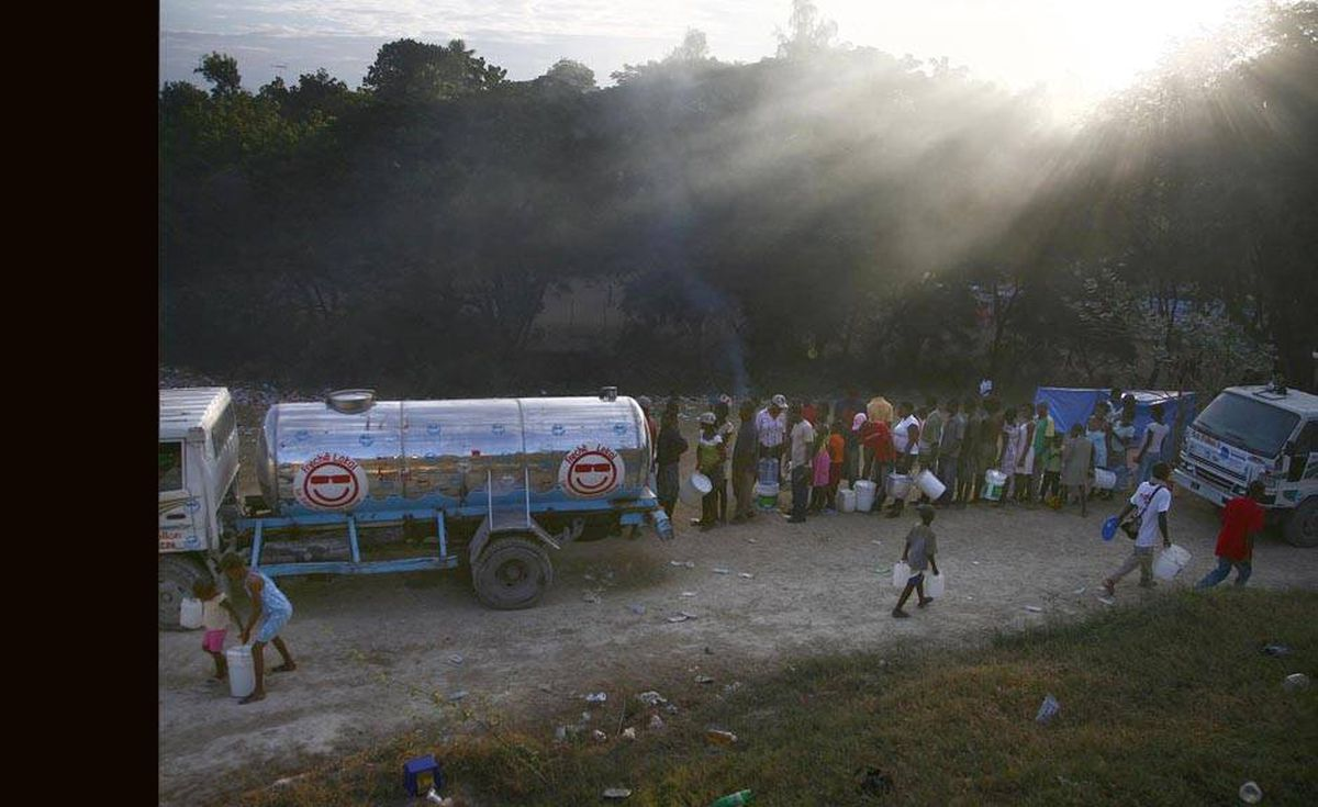 A group of people line up with containers to get water.