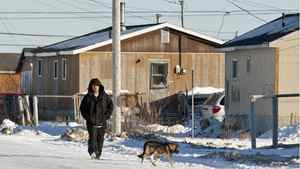 A man walks down the street in Attawapiskat, Ont., on Nov. 29, 2011.