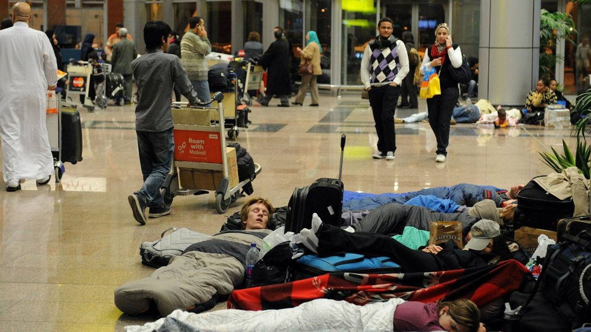 Tourists and Egyptians stranded at Cairo s international airport sleep late on January 29, 2011 as they can t leave the airport due to the curfew being brought forward in the Egyptian capital following anti-government riots.