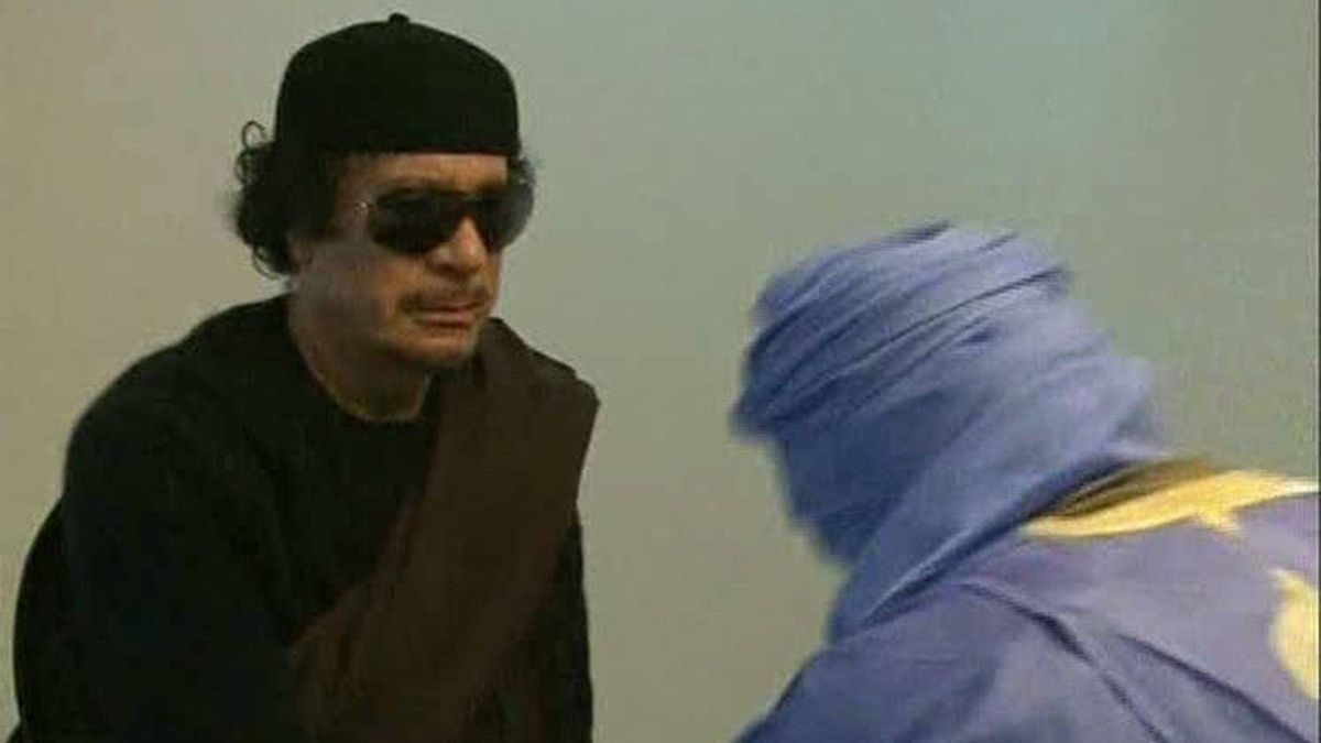 In this image from television broadcast by Libyan television on Tuesday June 7, 2011, Libyan leader Moammar Gadhafi greets unidentified people at an unknown location.
