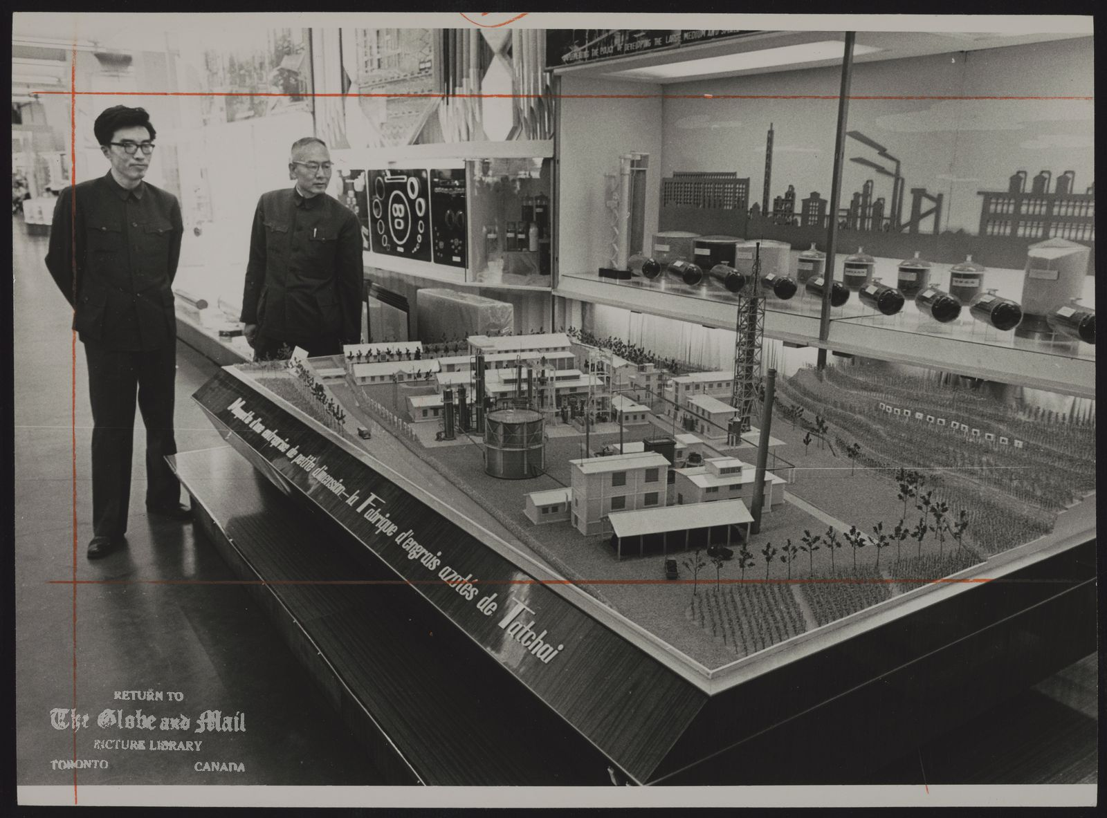 The notes transcribed from the back of this photograph are as follows: CANADIAN NATIONAL EXHIBITION China Pavilion (LI Yung-ting, right, with interpreter, examines model of a nitrogen factory that is patrol an exhibit by the People's Republic of China, at the Canadian National Exhibition.)