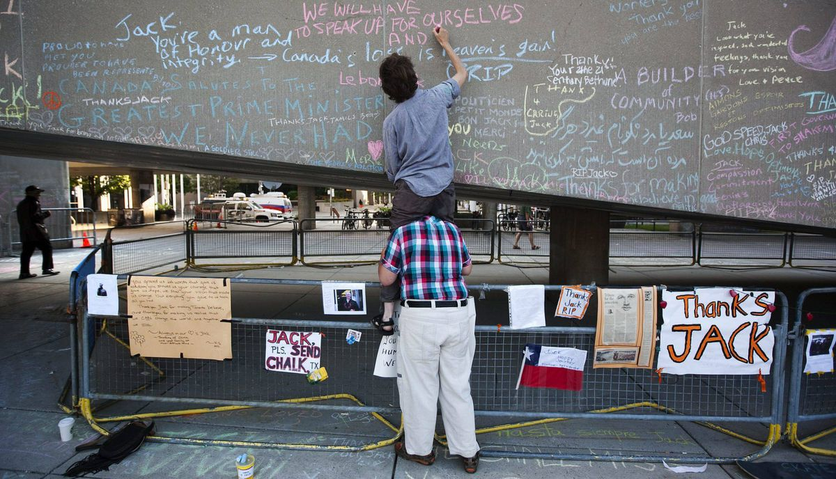 Mary Daniel sits on the shoulders of Marc Cannon to write a message of condolence in chalk at Nathan Phillips Square.