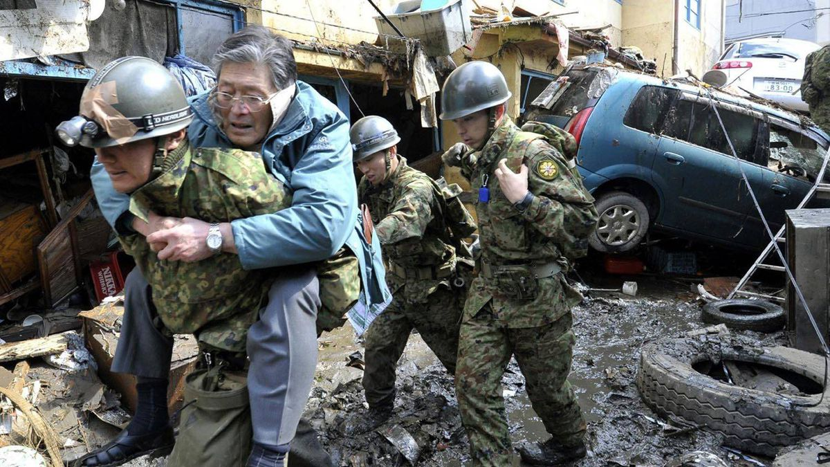 A man who's been stranded in a residence is carried on the back of a Japanese soldier to higher grounds at Kesennuma, northeastern Japan on Saturday.