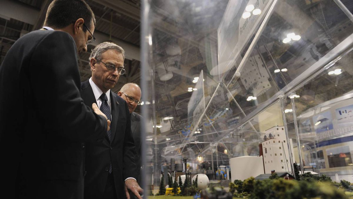 Federal Minister of Natural Resources Joe Oliver, second from left, takes in a display at the 2012 PDAC conference in Toronto.