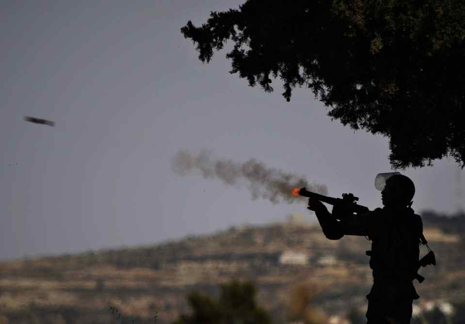 An Israeli soldier fires tear gas towards Palestinian demonstrators, not pictured, during a protest against the expansion of the nearby Jewish settlement of Halamish in the West Bank village of Nabi Saleh, near Ramallah.