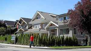 A man walks by a home in the Kitsilano neighbourhood of Vancouver, BC August 3, 2011.