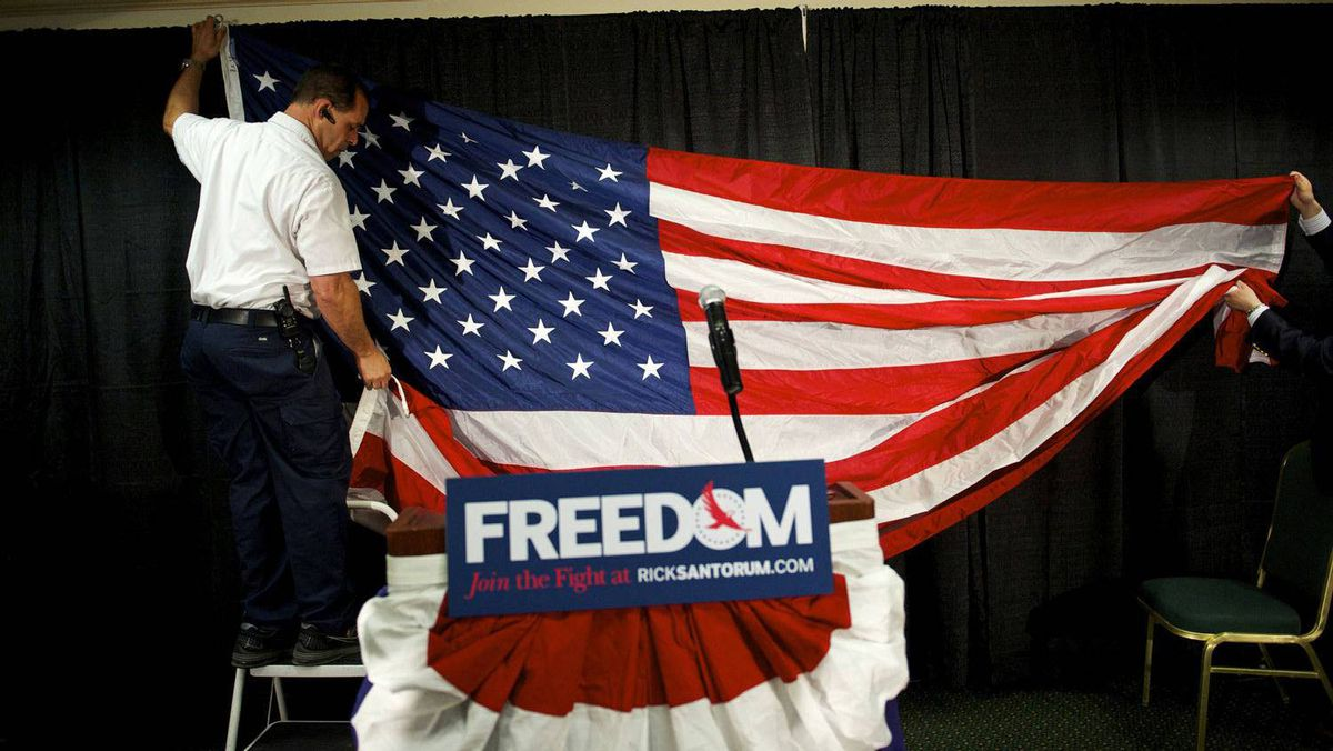 Workers hang a U.S. flag as the backdrop for conservative Rick Santorum's stage before his announcement that he is dropping out of the Republican presidential race in Gettysburg, Pa., April 10, 2012.