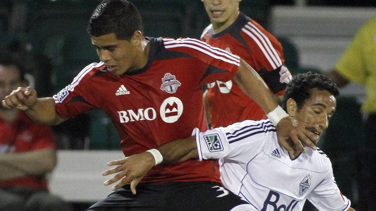 Vancouver Whitecaps' Camilo Sanvezzo, right, fights for the ball with Toronto FC's Junior Burgos, left, as Eric Avila looks on during the first half of a soccer match at the Walt Disney World Pro Soccer Classic Finals, Saturday, March 3, 2012, in Lake Buena Vista, Fla. (AP Photo/Reinhold Matay)