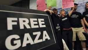 U.S. activists chant slogans as they hold placards during a news conference about an international flotilla to blockaded Gaza, in Athens, Monday, June 27, 2011.