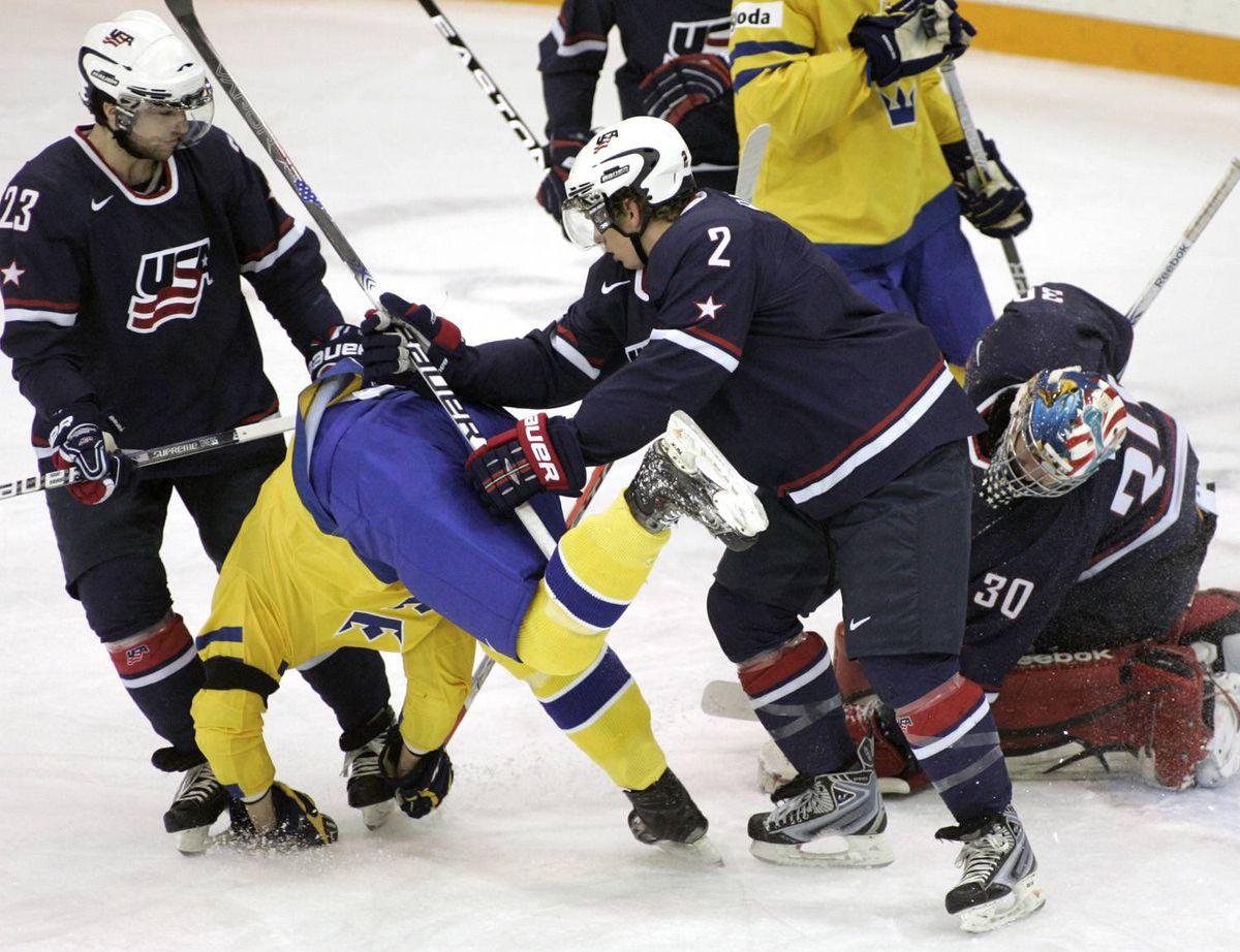 Team Sweden's Oliver Ekman Larsson, centre, is knocked over by Team USA's John Ramage, right, while Kyle Palmieri, left, and goalie Mike Lee look on during first period semifinal world junior hockey championship action in Saskatoon, Sask., Sunday, Jan. 3, 2010. THE CANADIAN PRESS/Geoff Howe