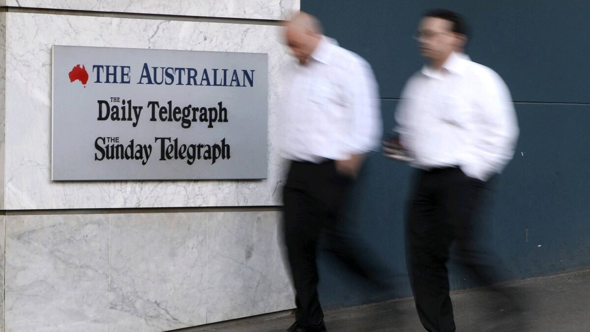 Two men walk past The News Ltd. offices in Sydney, Australia, Wednesday, June 20, 2012. The Australian arm of Rupert Murdoch's News Corp. said Wednesday it is making a US$2 billion bid to take full control of pay TV company Consolidated Media Holdings