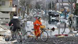 People ride bicycles with the backdrop of a flooded road in Shiogama, Miyagi prefecture, northern Japan, Sunday, March 13, 2011, two days after a powerful earthquake and tsunami hit the country's east coast.