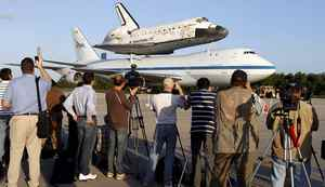 Members of the media photograph the space shuttle Discovery attached to a modified NASA 747 aircraft at Kennedy Space Center in Cape Canaveral