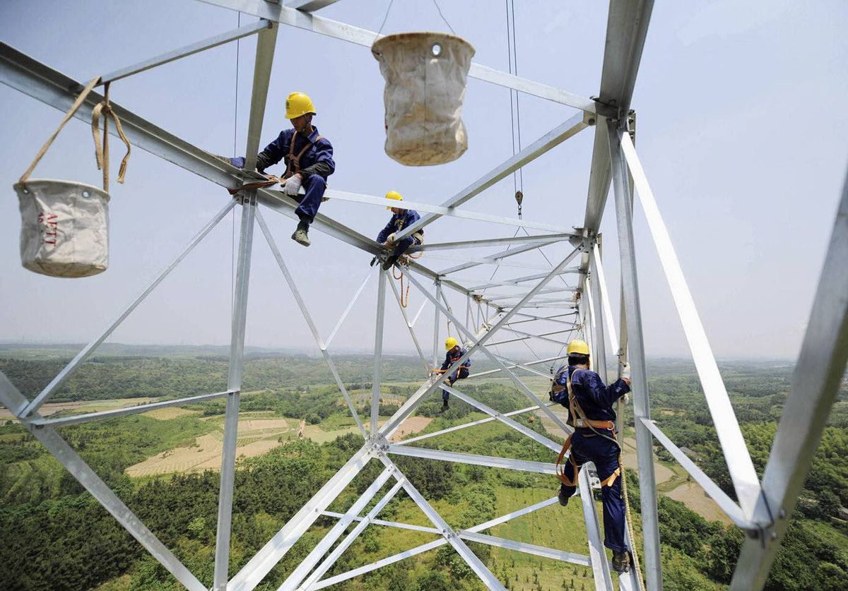 Workers install a high voltage electricity pylon in Xuancheng, Anhui province, China.