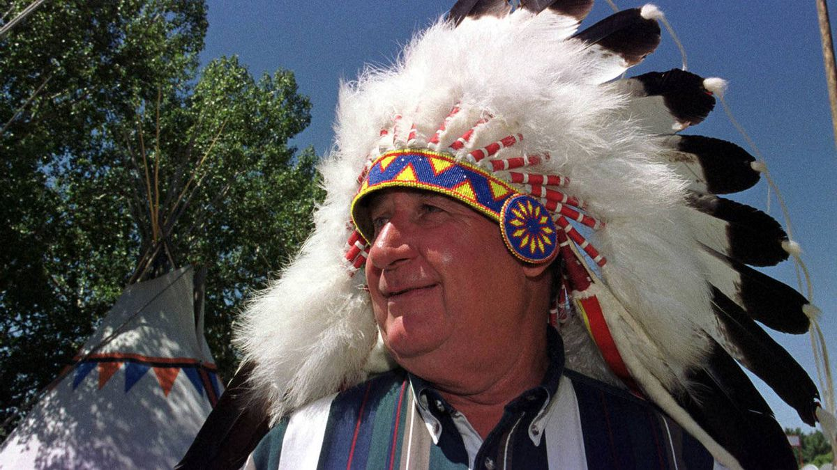 Mr. Klein looks towards a teepee after donning an Indian headress while he visited the 'Indian Village' at the Calgary Stampede on July 12, 2000.