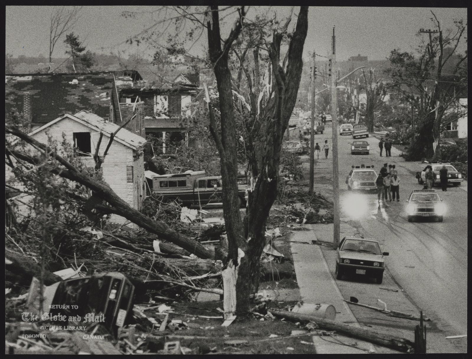 The notes transcribed from the back of this photograph are as follows: The fierce storm left houses and trees on Amaranth Street in Grand Valley in shreds.