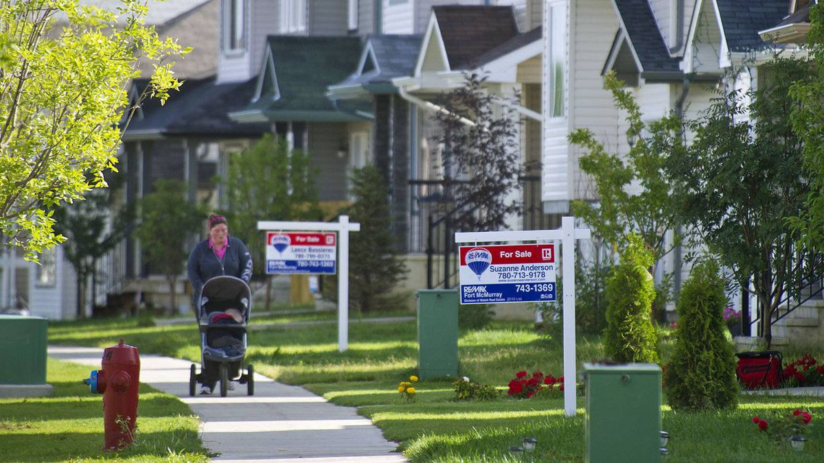A woman pushes a stoller past for-sale signs in Fort McMurray, Alta.,on Aug.29, 2010.