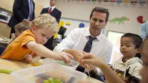 Ontario Premier Dalton McGuinty builds necklaces with Nathan Skinner, 3, left, and Alex You, 4, in a full day kindergarten class at Stoney Creek Public School in London, Ontario, October 8, 2010.