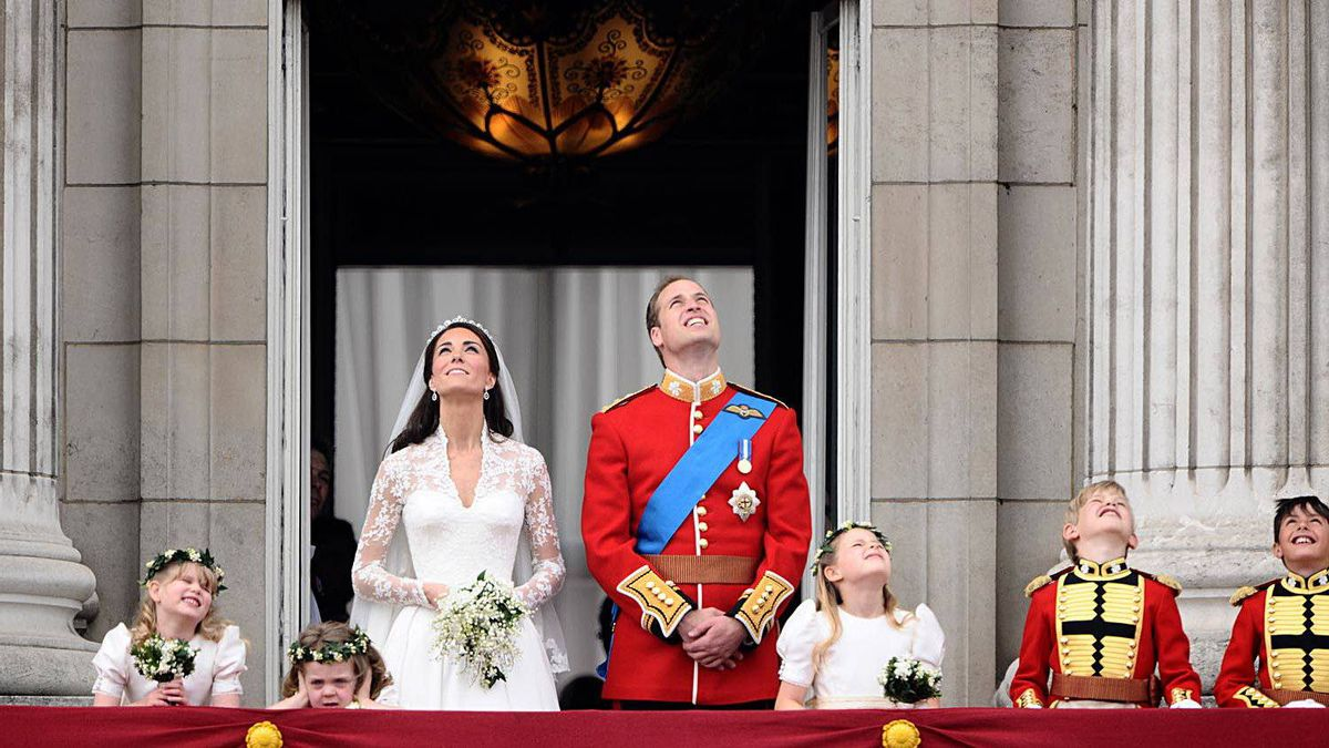 Prince William and his wife Kate, Duchess of Cambridge look up as the Royal Air Force perform a flypast while they stand on the balcony of Buckingham Palace in London, after their wedding ceremony, on April 29, 2011.