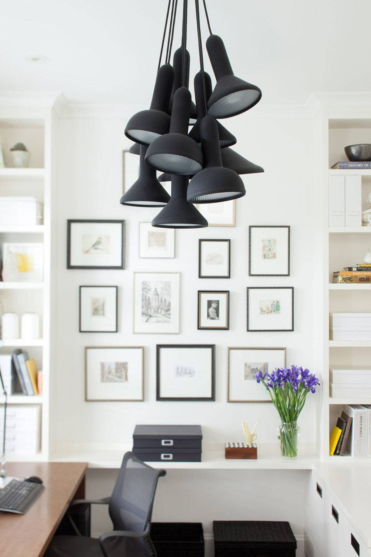 The playful utilitarianism of the Torch Light fixture counters the plain white of the office background, leaving the matte black finish to reference the room's other dark elements--carpet, hardware, computers, and Eames chairs.
